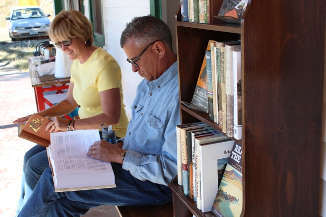 The Abeytas, from just up the road, take a moment to sample the porch library.